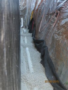 """Perforated Drain Pipe bedded in min 3"""" of gravel.  Piles of gravel over pipe is to hold pipe in place during grading as otehrwise as you lift the work end, the parts you have already levelled will move.  Pipe has to be left exposed for inspection."""