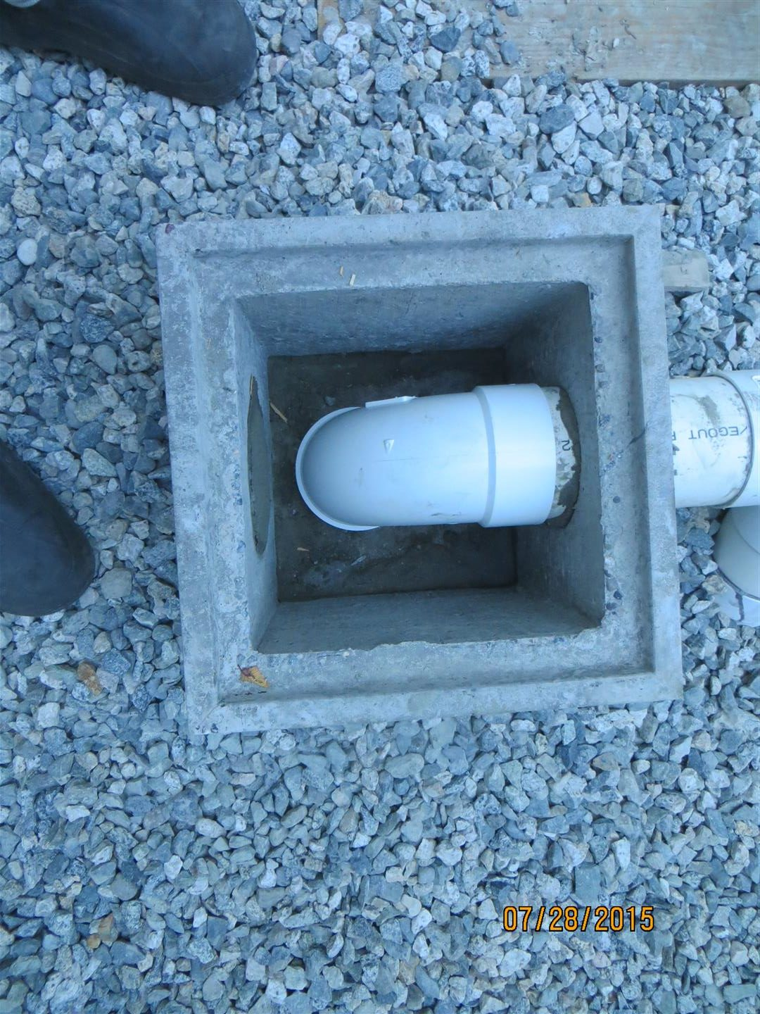 Inside of drain box has dry fit 90º elbow.  This allows for removal during cleaning of line.  Elbow prevents floating debris from entering system.