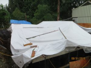 Top side of tarp is strapped down to supports with furring strips