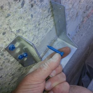Beam hanger attached to the concrete foundation with this bitty Titan hex screws.  As a result, I made sure the surface was very smooth before drilling and attaching hanger so each screw would have max holding power.