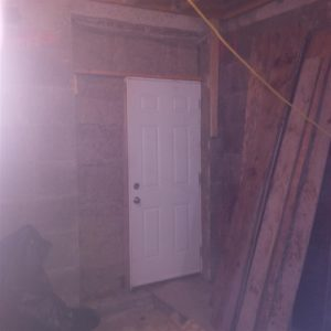 """Construction door in the much larger opening that will provide a 48"""" x 96"""" Exit door to the basement walk-up at the end of construction."""