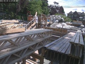 Beams roughly in pace and trusses stacked in bundles on top plates