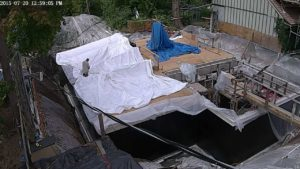 Tarp draped across 2x4 stringers and stapled in place